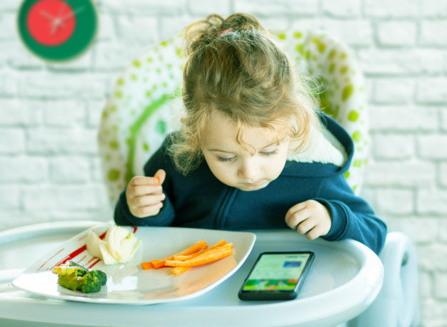 Baby glued to smartphone while eating